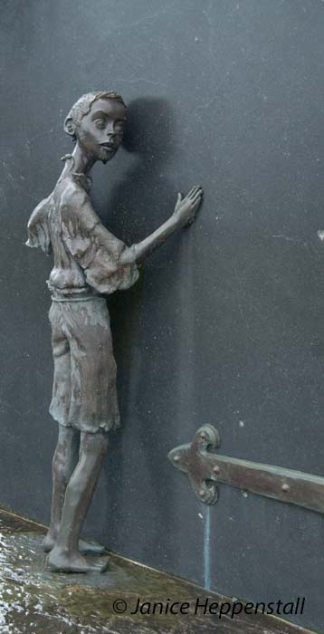 Part of memorial to the Great Famine of 1845-1850 showing small orphaned boy waiting at a door.