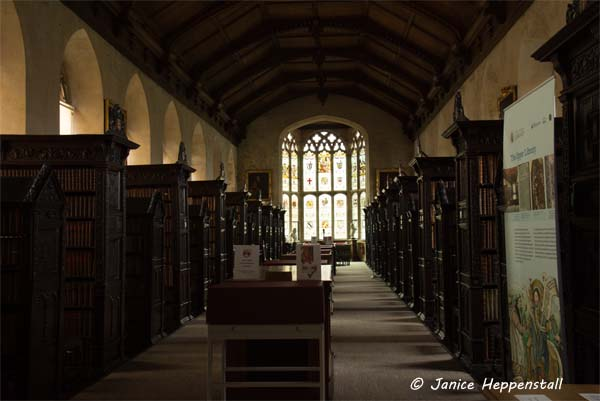 Ancient library with rows of dsecorative dark wood shelves and a large stained glass window at the far end
