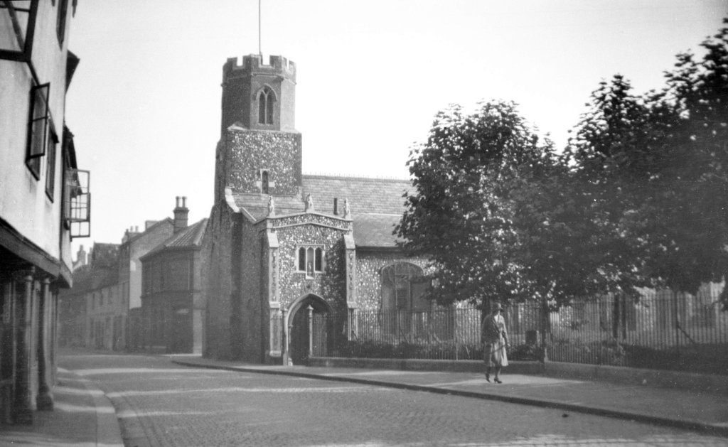 Norwich street in 1931 featuring the medieval church St James Pockthorpe and churchyard