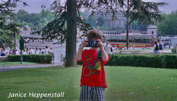 Small boy with camera, taking photograph
